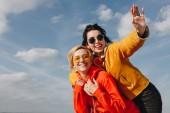 usmívající se dívky, vezou a mával v Saint michaels mount, Normandie, Francie