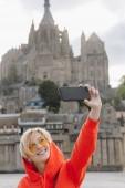 Fotografia Ragazza felice prendendo selfie su smartphone near Saint michaels mount in Normandia, Francia