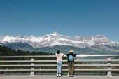 Photo back view of girls standing near fence and looking at majestic snow-capped mountains, mont blanc, alps
