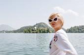 Fotografie krásná mladá žena v brýle, stojící nedaleko malebného jezera v horách, bled, Slovinsko
