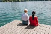 Hátulnézet a két fiatal stílusos nők ül a fa mólón-tónál, bled, Szlovénia