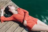 szép stílusos lány, napszemüveg, fából készült móló tó közelében fekvő felülnézet