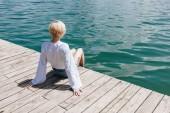 zadní pohled na stylová holka sedí na dřevěném molu u jezera bled, Slovinsko