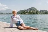 krásná mladá žena v sluneční brýle spočívající na dřevěném molu v malebné horské jezero bled, Slovinsko