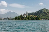 Fotografie old architecture and green trees at bank on scenic mountain lake, bled, slovenia