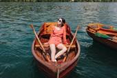 Fotografia bella ragazza in occhiali da sole che si siede sulla barca di legno sul lago