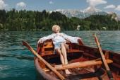 gyönyörű fiatal nő, pihenő, csónak csendes hegyi tó, bled, Szlovénia