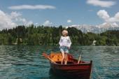 gyönyörű fiatal nő, napszemüveg, állva a hajó csendes hegyi tó, bled, Szlovénia