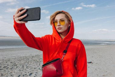 beautiful girl in red hoodie taking selfie on beach, saint michaels mount, France