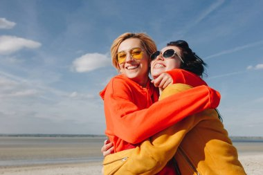 smiling female friends embracing on sandy beach, Saint michaels mount, Normandy, France