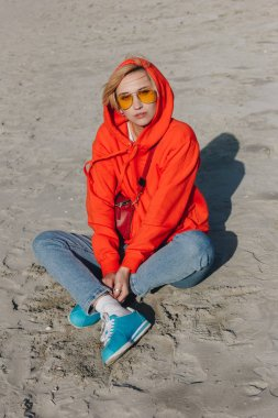 stylish girl in red hoodie sitting on sandy beach, Saint michaels mount, Normandy, France