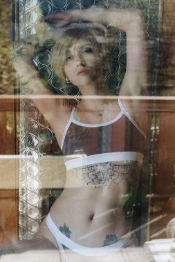 view through the glass of beautiful sexy tattooed girl in underwear looking at camera