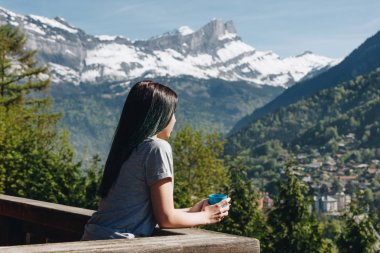 girl holding cup while standing on balcony and looking at scenic mountains, mont blanc, alps