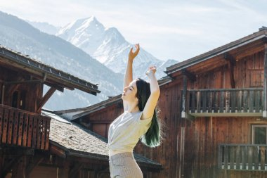 Side view of beautiful young woman raising hands while standing between wooden houses in mountain village, mont blanc, alps stock vector