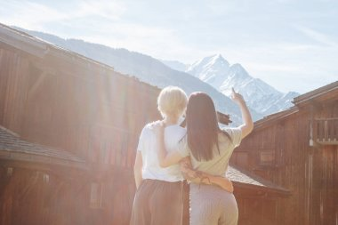 back view of young women embracing and looking at majestic mountains, mont blanc, alps