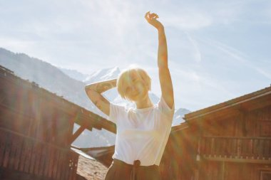 beautiful happy young woman raising hand and looking at camera while standing between wooden houses in mountain village, mont blanc, alps