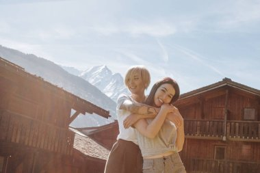 beautiful happy girls hugging while standing between wooden houses in mountain village, mont blanc, alps