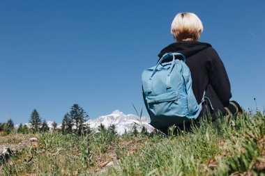 Back view of young female traveler with backpack resting on grass in mountains, mont blanc, alps stock vector