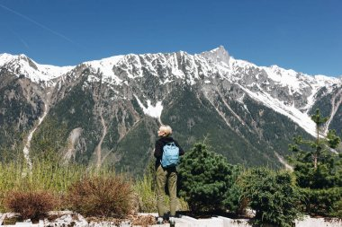 back view of young woman with backpack standing in majestic snow-capped mountains, mont blanc, alps