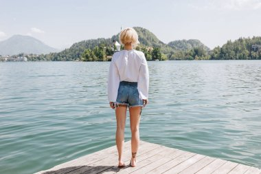 back view of young woman standing on wooden pier and looking at scenic mountain lake, bled, slovenia