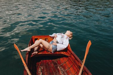 high angle view of young woman relaxing in wooden boat on lake