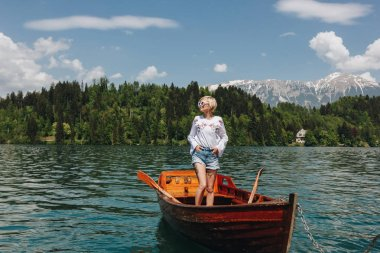 beautiful young woman in sunglasses standing in boat at tranquil mountain lake, bled, slovenia