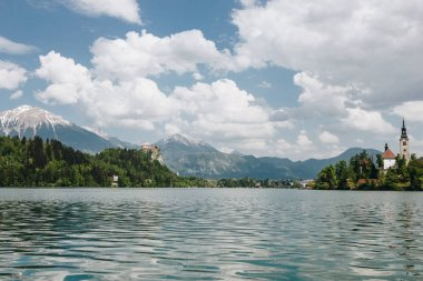 beautiful landscape with calm mountain lake, peaks and buildings, bled, slovenia