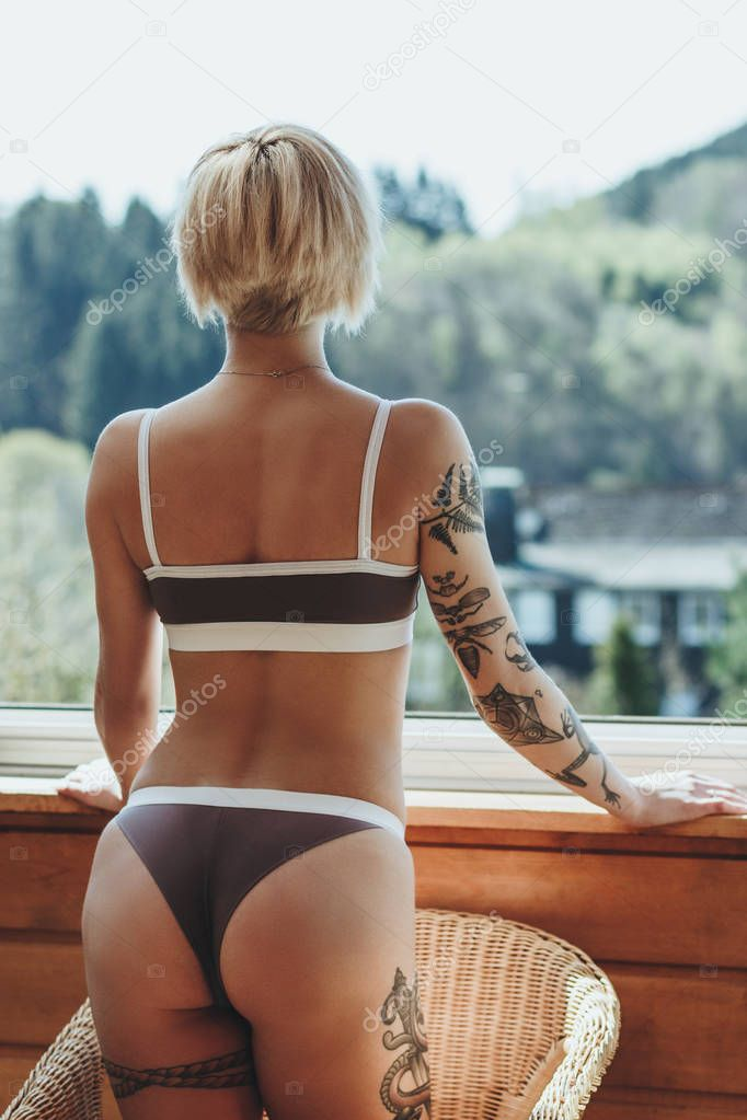 back view of sexy girl in underwear standing on balcony and looking at scenic mountains