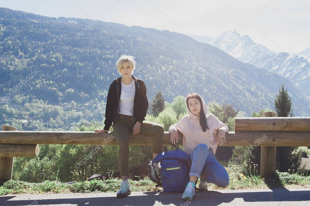 beautiful young female travelers looking at camera while resting on wooden fence in scenic mountains, mont blanc, alps