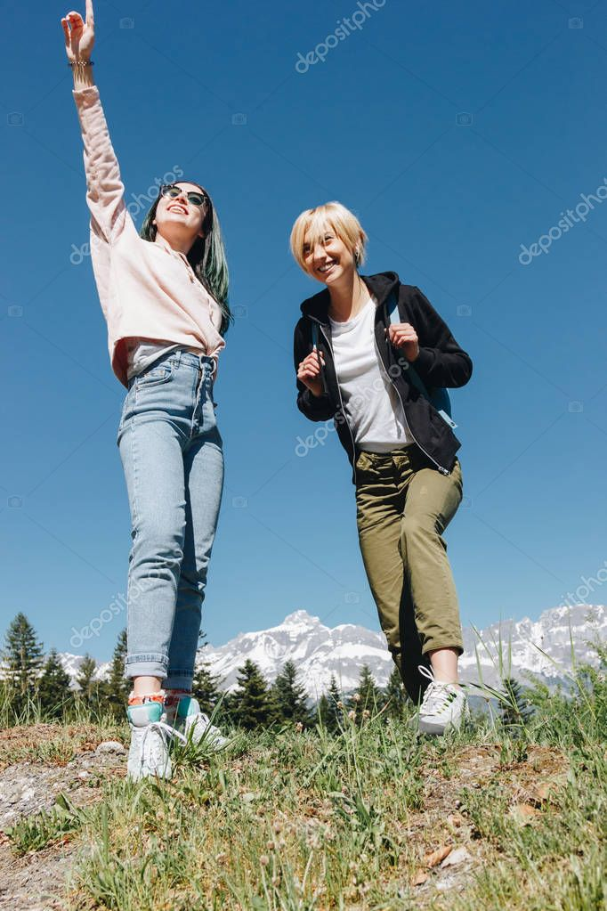 low angle view of beautiful happy female travelers standing together in majestic mountains, mont blanc, alps