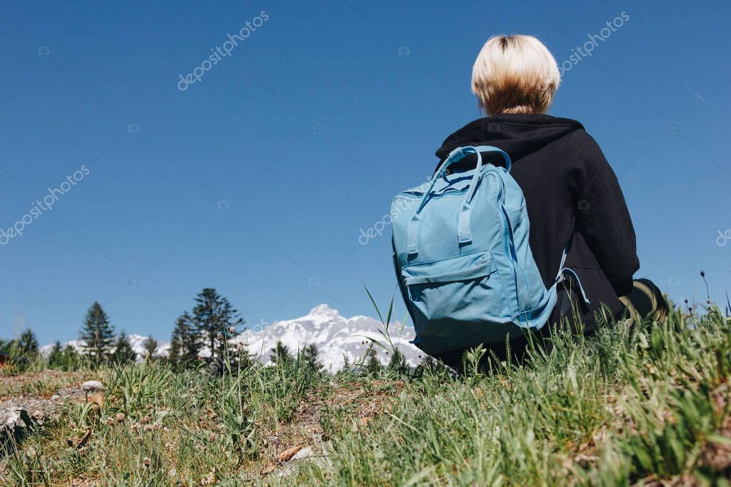 back view of young female traveler with backpack resting on grass in mountains, mont blanc, alps
