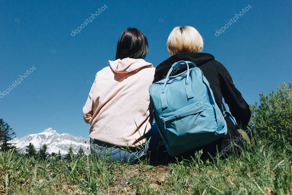 back view of young female travelers resting on grass in mountains, mont blanc, alps