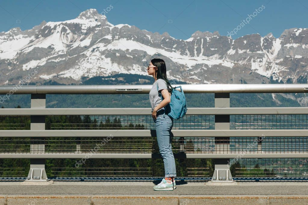 side view of girl with backpack standing near fence in majestic majestic, mont blanc, alps