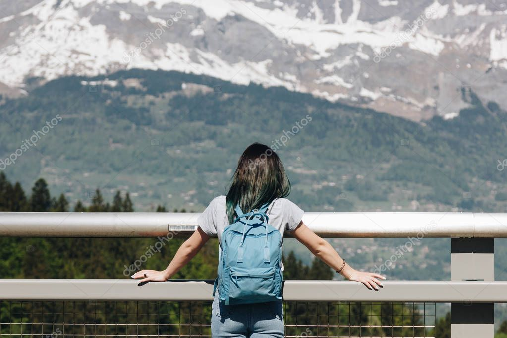 back view of girl with backpack looking at majestic scenic mountains, mont blanc, alps