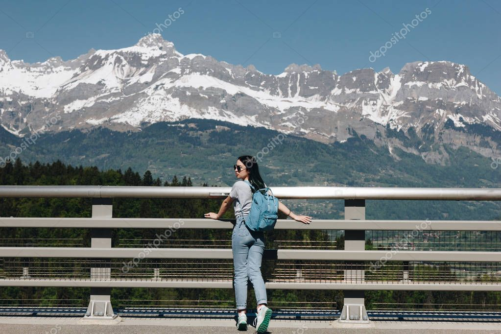 back view of young woman with backpack standing in beautiful scenic mountains, mont blanc, alps