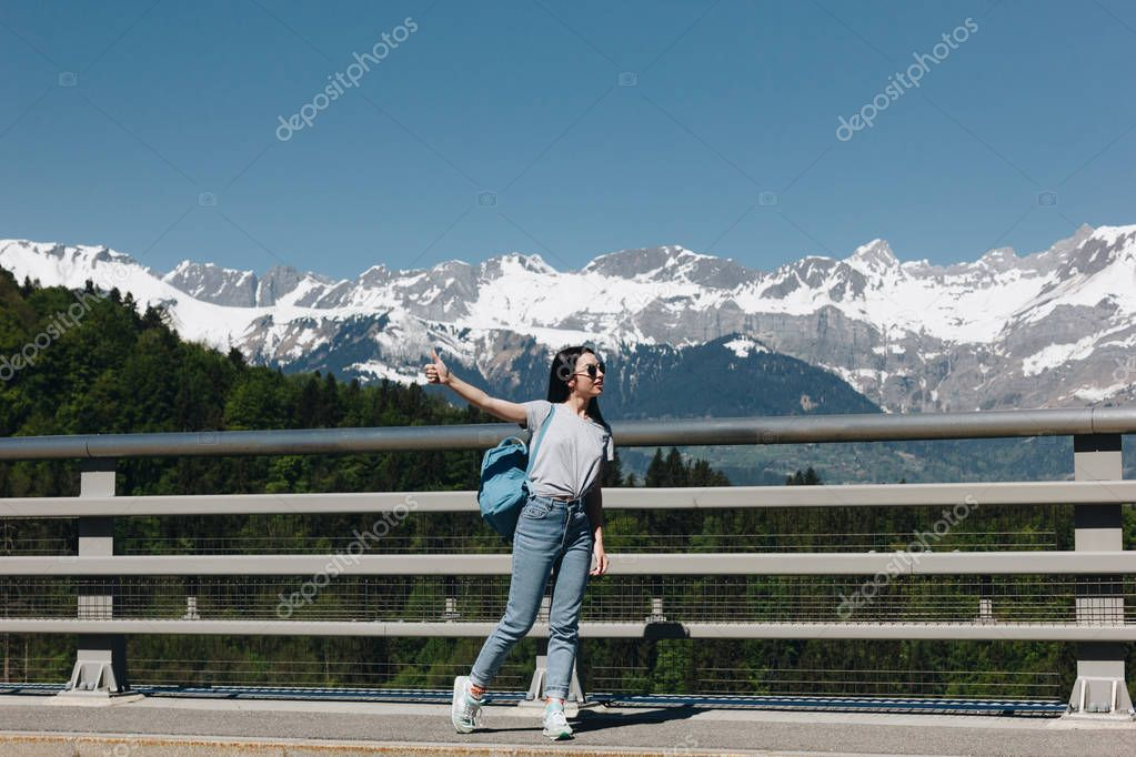 full length view of beautiful girl with backpack looking away in majestic snow-capped mountains, mont blanc, alps