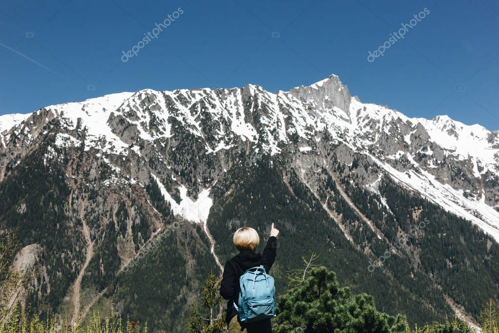 back view of young woman with backpack pointing with finger at majestic snow-capped mountains, mont blanc, alps