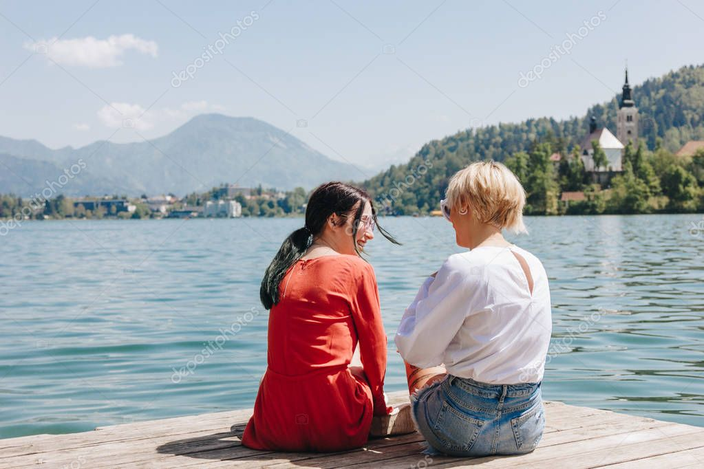 back view of stylish girls sitting on wooden pier near tranquil mountain lake, bled, slovenia