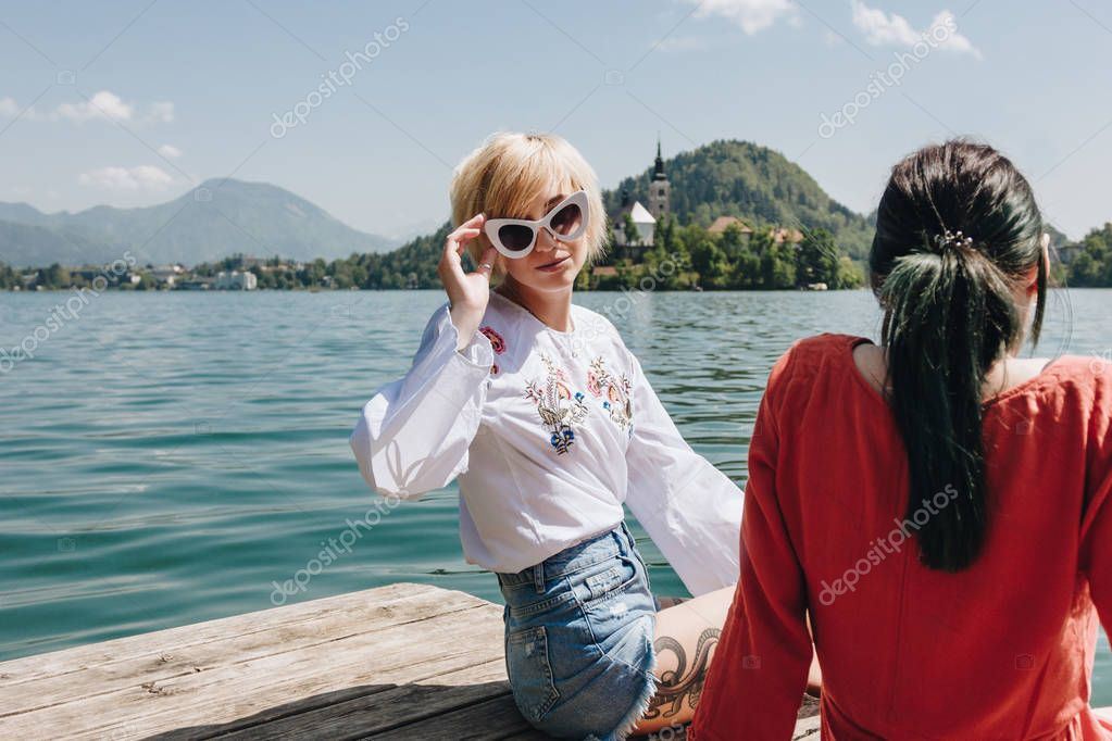beautiful girl in sunglasses looking at camera while sitting with girlfriend on wooden pier at mountain lake, bled, slovenia