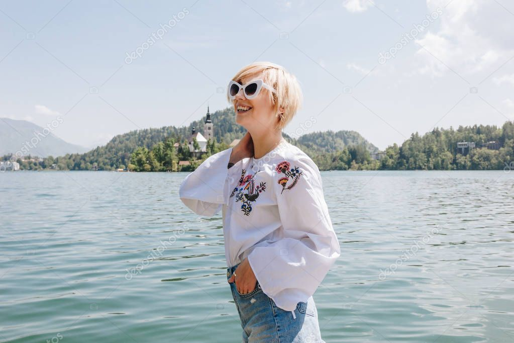 beautiful smiling young woman in sunglasses standing near majestic mountain lake, bled, slovenia