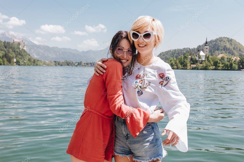 beautiful young women in sunglasses hugging and smiling at camera while standing near tranquil mountain lake, bled, slovenia