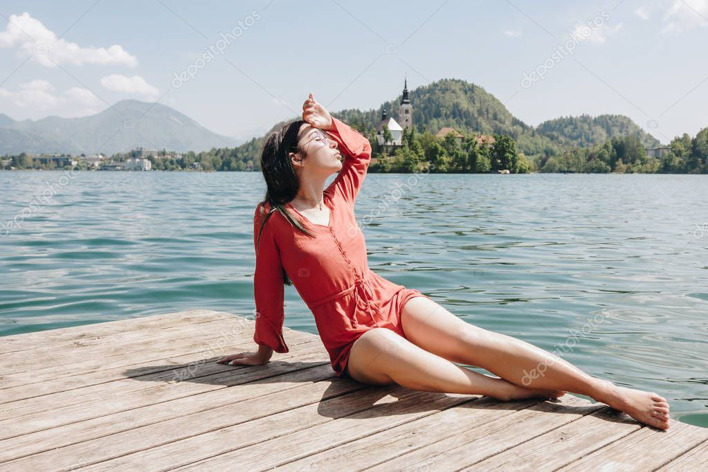 beautiful young woman resting on wooden pier at scenic mountain lake, bled, slovenia