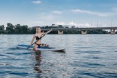 athletic beautiful girl paddle boarding on river