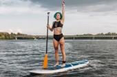 Fotografie tätowierte Sportlerin winken und Paddle boarding am Fluss im Sommer