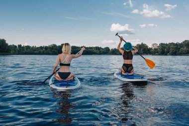 back view of girls surfing on paddle boards on river