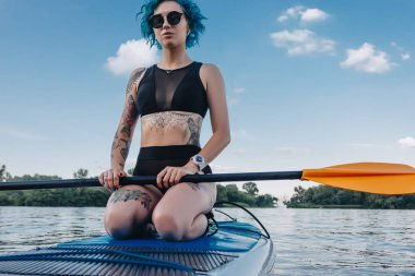 attractive tattooed girl in sunglasses sitting on paddle board on river