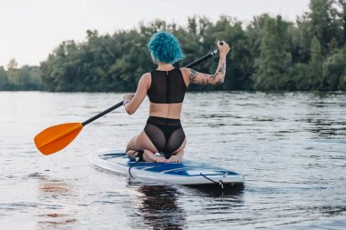 back view of girl with blue hair sitting on paddle board on river