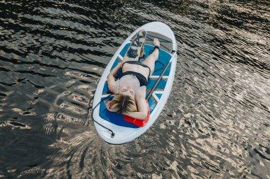 Attractive tattooed woman in bikini lying on sup board on water stock vector