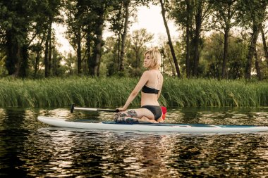 Beautiful blonde girl sitting on paddle board on river stock vector