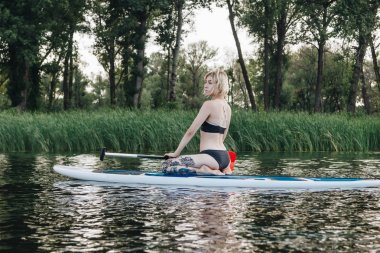 blonde tattooed girl sitting on paddle board on river